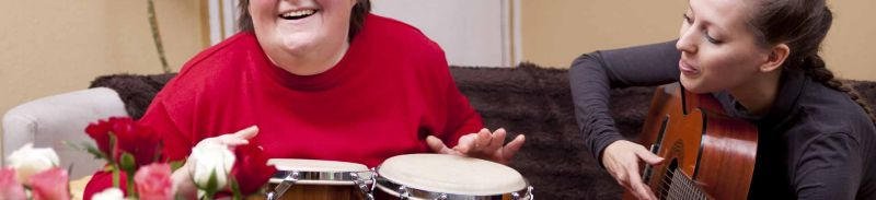 An adult with learning disabilities playing the drums